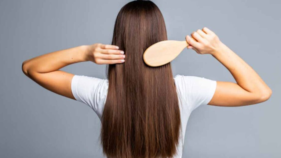 rear view of girl combing hair